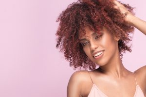 medium closeup curly red pink hair african american woman pink background pink strappy tank top best hair color for thin hair toppik hair blog