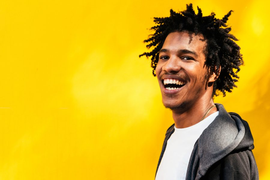 laughing smiling man african american gray hoodie white tee shirt bright yellow background tousled dreads hairstyle 2020 hair trends for men and past styles toppik hair blog