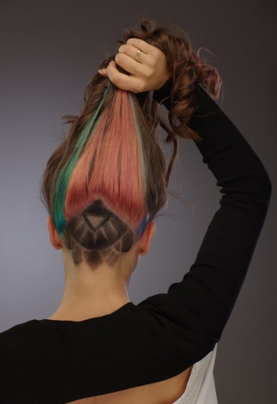 Woman showcases her Geometric shaved hair design with Color