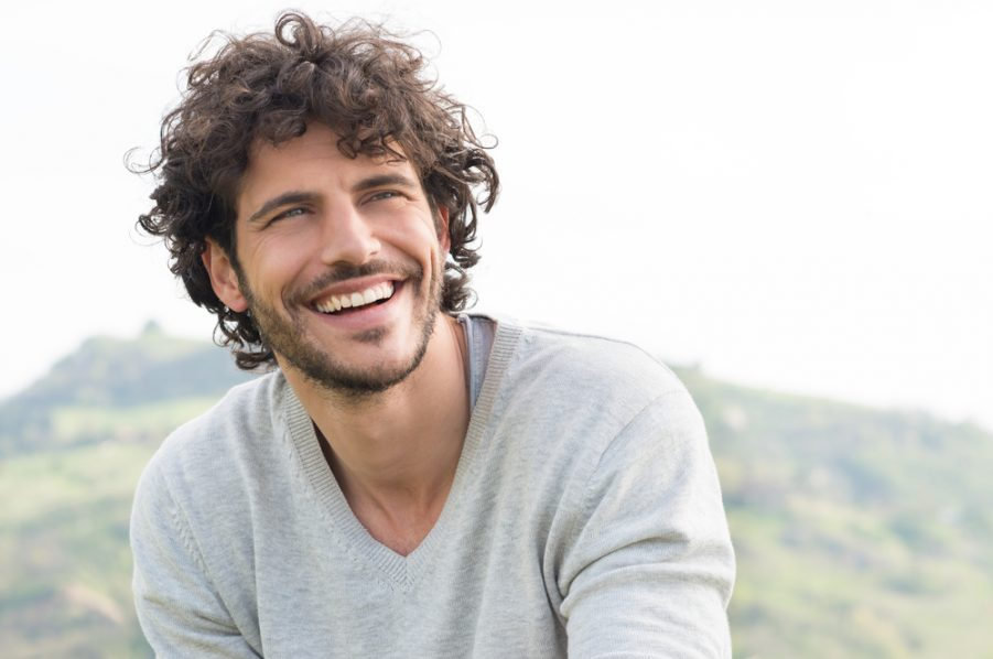 smiling handsome man brown curly hair outside mountain background 70s grow-out hairstyle 2020 hair trends for men and past styles toppik hair blog