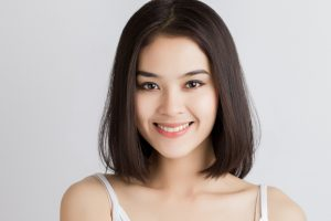 smiling asian woman shoulder length bob chocolate brown hair white background best hair color for thin hair toppik hair blog