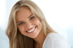 closeup smiling young woman white teeth long neutral blonde hair best hair color for thin hair toppik hair blog