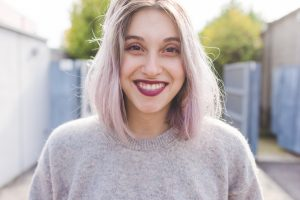 closeup smiling woman dark lipstick gray sweater outside gray pink hair color best hair color for thin hair toppik hair blog