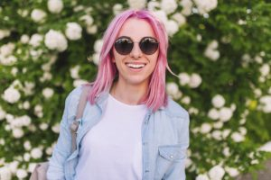 medium closeup smiling woman bright pink hair sunglasses light blue denim shirt flowers background best hair color for thin hair toppik hair blog