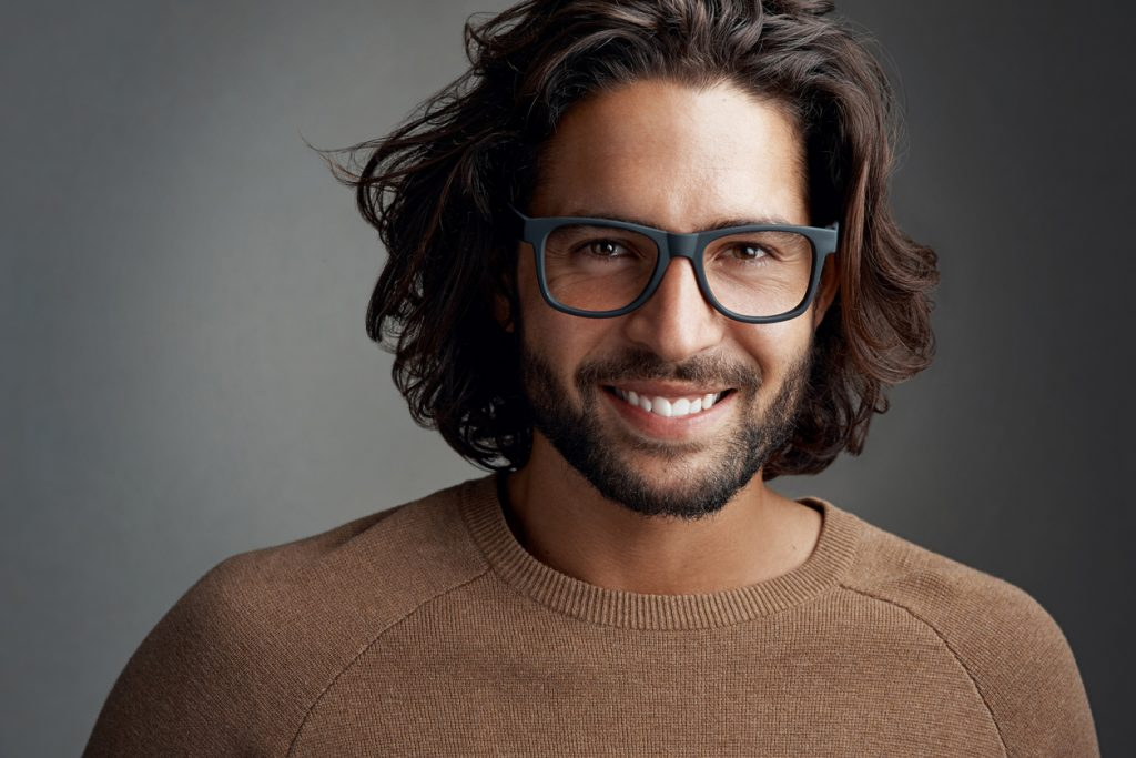 closeup man long shag haircut brown hair black frame glasses tan sweater dark gray background shag haircuts for men and women toppik hair blog
