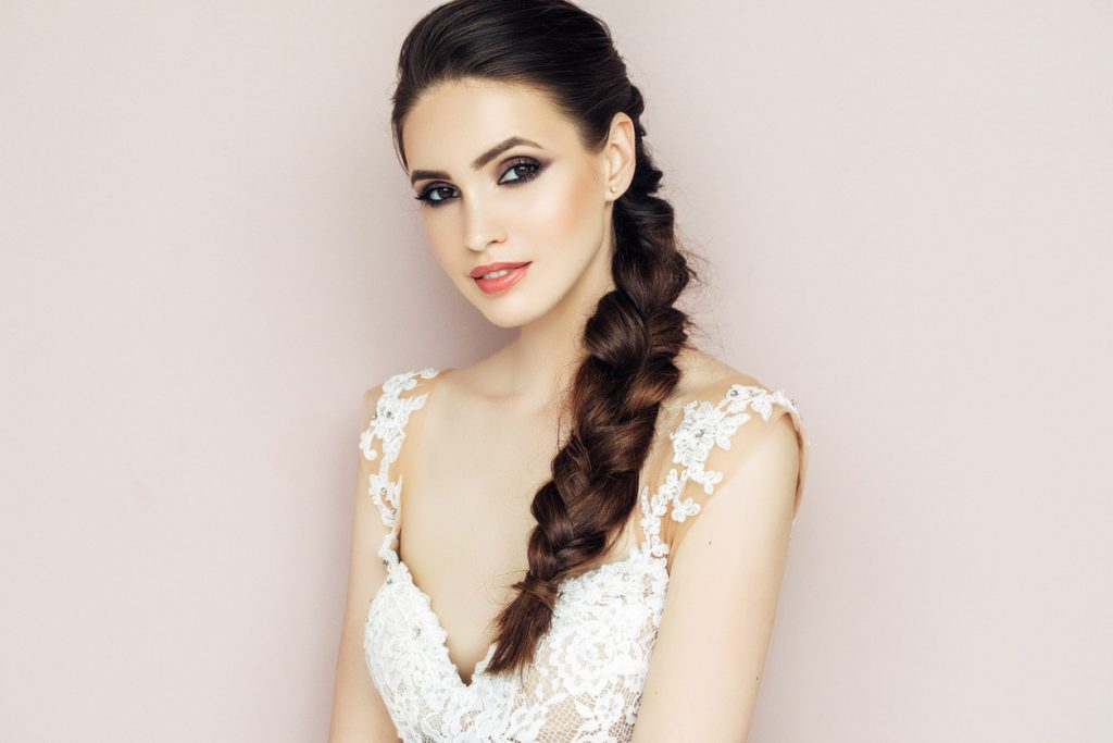 woman long dark brown hair side swept braid white lace shirt hairstyles for valentines day toppik hair blog