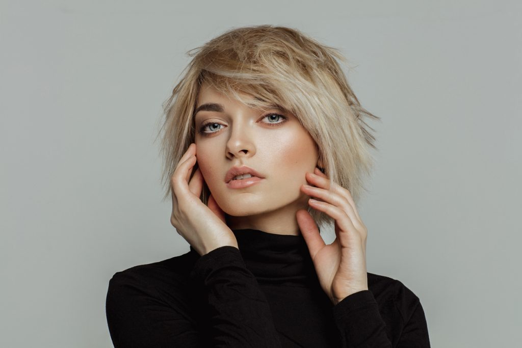 woman blonde short shag hair with bangs black turtleneck gray background shag haircuts for men and women toppik hair blog