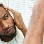 man examining hairline in mirror beard african american can stress cause hair loss toppik hair blog
