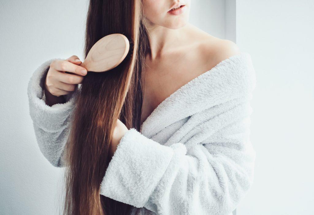 woman brushing long shiny hair white bathrobe natural bristle brush 6 healthy scalp tips for better hair toppik hair blog