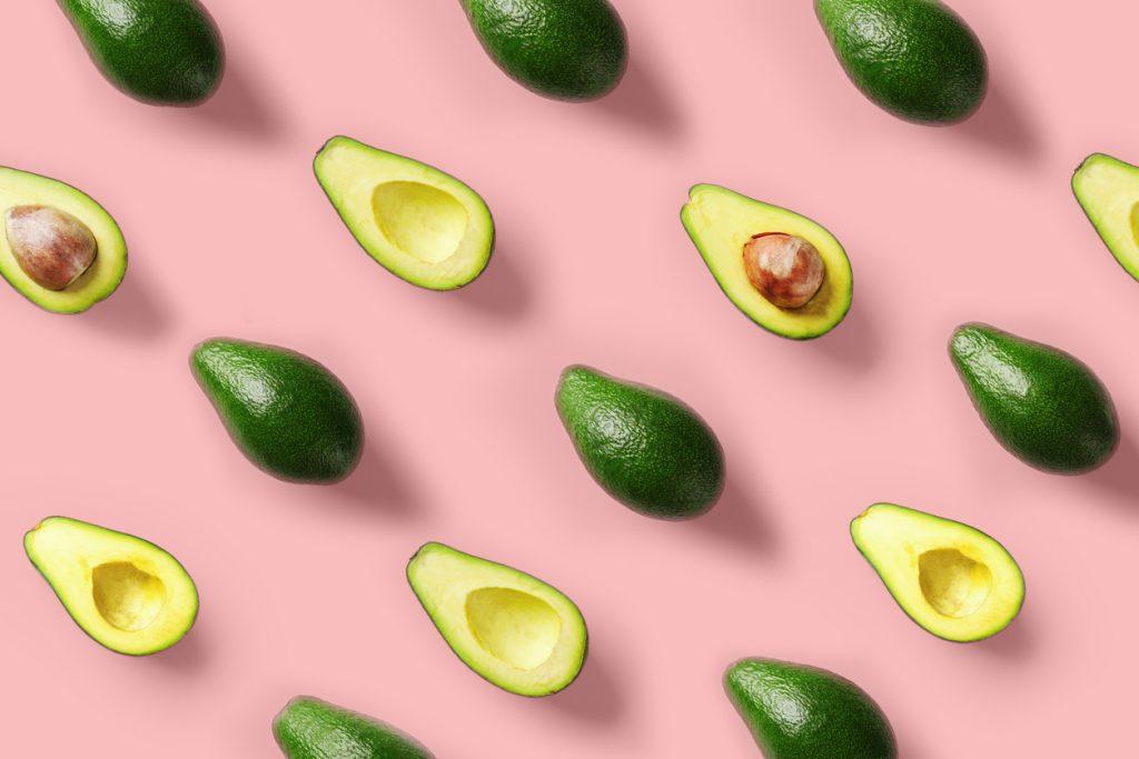 avocados halves pits flat lay pastel pink background best DIY hair thickening mask toppik hair blog