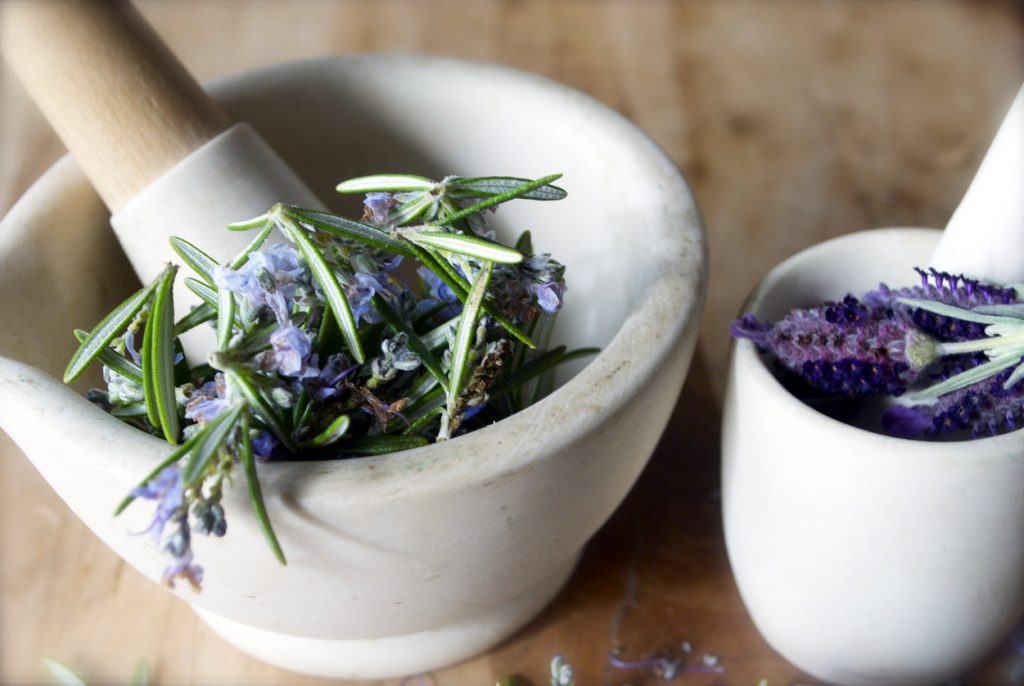 closeup fresh lavender flowers rosemary leaves in white ceramic mortar and pestle wood tabletop best DIY hair thickening mask toppik hair blog