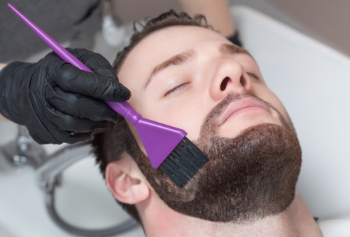 man having premature gray hair treatment of hair dye applied to his beard Toppik blog