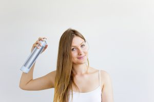 Woman applying dry shampoo and styles her hair Toppik Blog